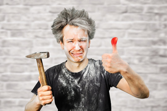 Dirty young builder guy fail is hold a hammer, hit the finger on brick wall background at home during repairs