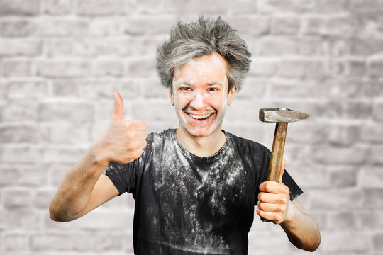 Dirty young builder guy in plaster is hold a hammer on brick wall background at home during repairs