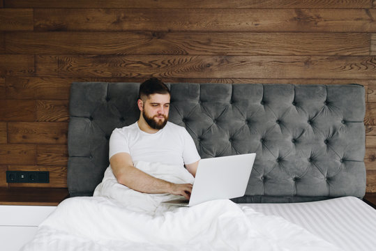 Young caucasian man working on his laptop in bed from home