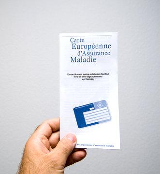 PARIS, FRANCE - JUN 26, 2018: Man holding the Carte europeen d'assurance maladie insurance healthcare card against white background