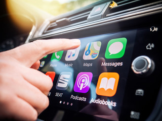 PALMA DE MALLORCA, SPAIN - MAY 10, 2018: Woman pressing Apple Maps button on the Apple CarPlay main screen in dashboard during driving on Spanish holiday highway - large digital display screen
