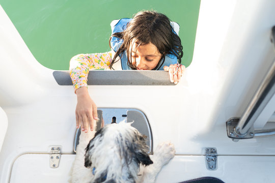 Young Girl in a life jacket climbing into boat with her wet puppy