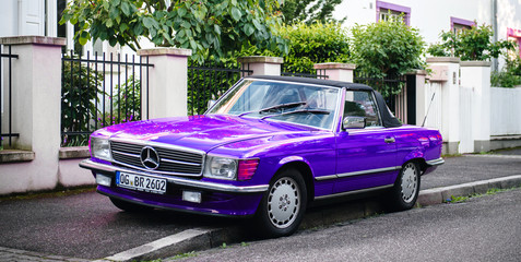 Strasbourg, France - May 19, 2017: Beautiful vintage purple convertible cabriolet Mercedes-Benz 300 Sl parked in front of French luxury house in calm neighborhood