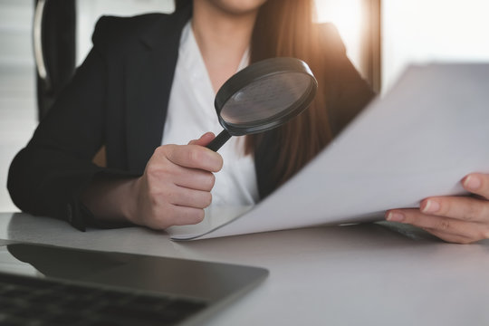 Business woman using magnifying to review balance sheet annual. audit and Check integrity before investment concept.