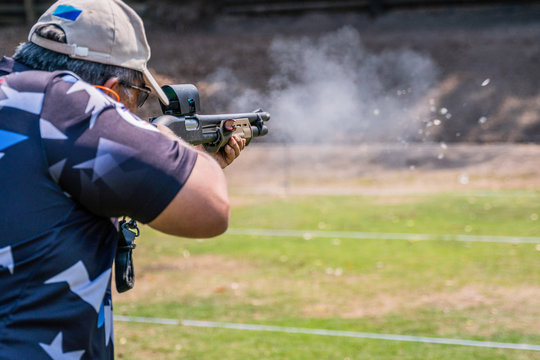 selective focus of man holding and fire shotgun in shooting range of gun shooting competition