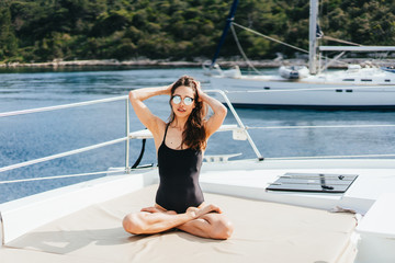 Young healthy and calm woman doing yoga on sailing yacht boat in sea at island background