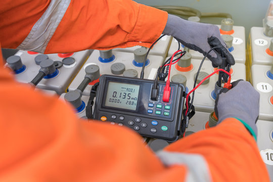 Electrical technician operator is measuring voltage and internal resistance of battery for performance monitoring at offshore oil and gas production platform.