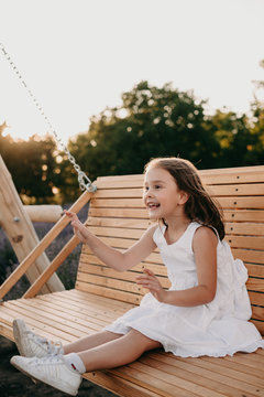 Cheerful caucasian girl dressed in a white dress is sitting in a swing having fun in a summer evening