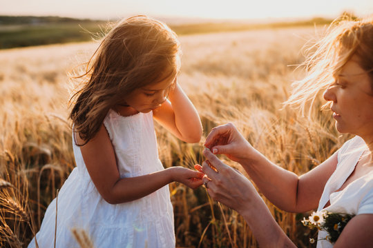 Beautiful caucasian girl and her mother posing against the sunshine on a wheat field holding some seeds