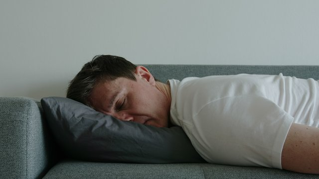 Portrait of young depressed man on a pillow