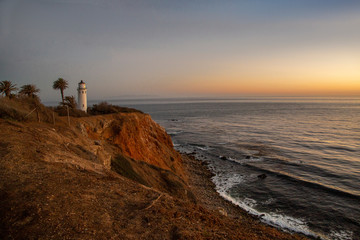 Lighthouse sitting on the coastline cliff at late sundown near LA, California
