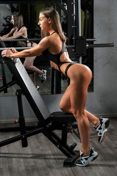 girl doing fitness in the gym on the background of a mirror