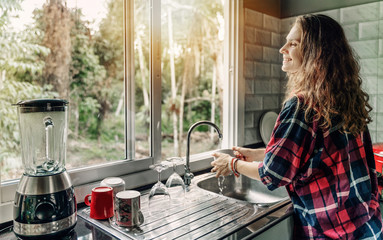 A woman washes dishes in her house, a sink in front of a window overlooking a summer garden