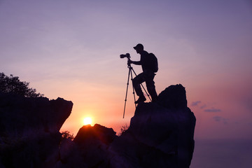 Photographer climbing on the top of the mountain to take a picture at sunset.