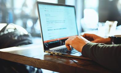 closeup mans hands freelancer sitting in cafe working laptop