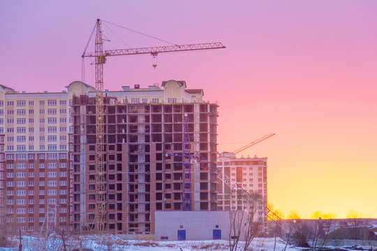 winter morning, the construction of multi-story frame houses with tower cranes