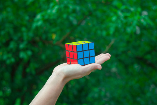 POIANA TEIULUI, ROMANIA - JULY 16, 2018: hand holding Rubik cube puzzle against a green tree background