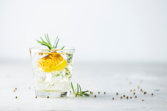 Charred Lemon, Rosemary and Coriander Gin and Tonic is a flavors are perfectly balanced refreshing cocktail. on light background, close up. Summer drinks and alcoholic cocktails