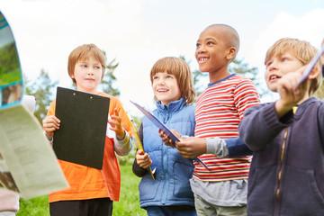 Kinder mit Klemmbrettern auf Schnitzeljagd