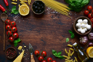 Traditional ingredients of italian cuisine : pasta, cheese,tomatoes,garlic,olive oil, basil and lemons. Top view with copy space. Fotomurales