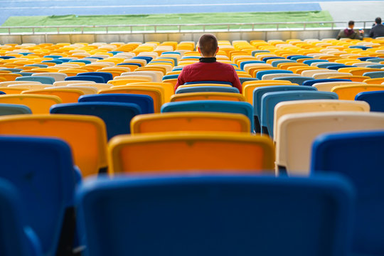 spectators watch football in a half-empty stadium