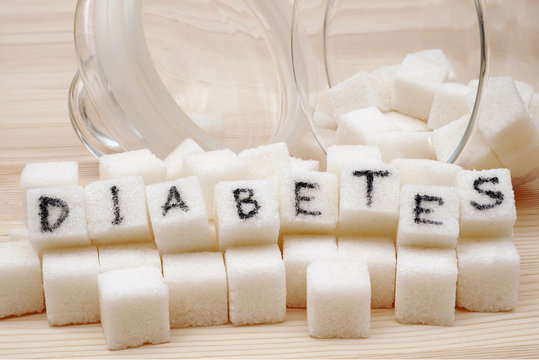 close-up on sugar cubes spilled from overturned glass sugar bowl with text diabetes on cubes on wooden background