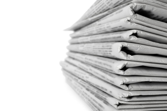 Stack of newspapers on white background, closeup. Journalist's work