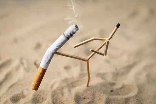 stop smoking concept - match man kick off a burning cigarette