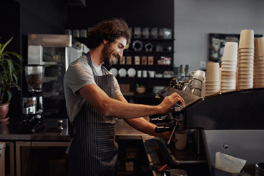 Smiling man with apron preparing coffee for customer in his small business