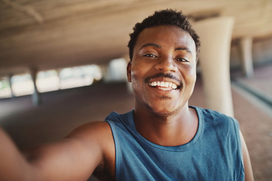 Portrait of a smiling young african american man taking selfie after jogging at outdoors