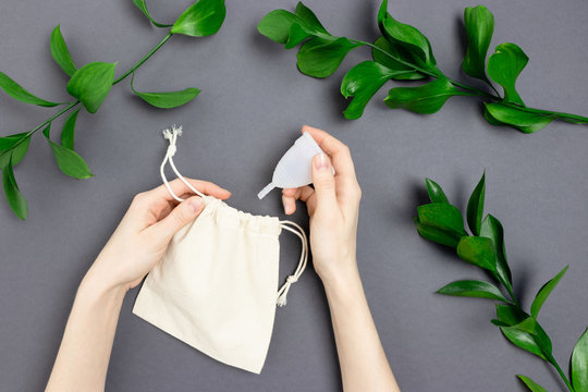 Female hands take menstrual cup from canvas bag. Frame made of green leaves on dark gray background.