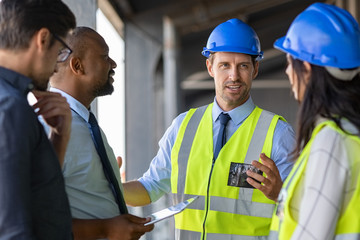 Engineers and architects in conversation at building site