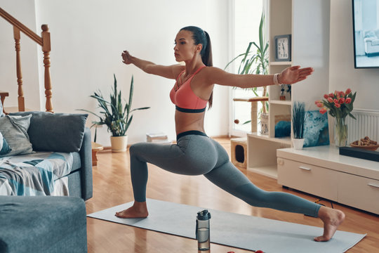 Sensual young woman in sports clothing working out while spending time at home