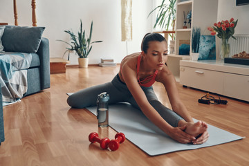 Attractive young woman in sports clothing stretching on exercise mat while spending time at home