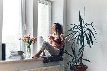 Thoughtful young woman in cozy pajamas looking through the window while resting at home