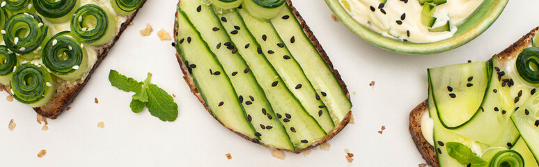 top view of fresh cucumber toasts with seeds, mint leaves near yogurt on white background, panoramic shot