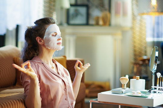 relaxed elegant woman with facial mask meditating