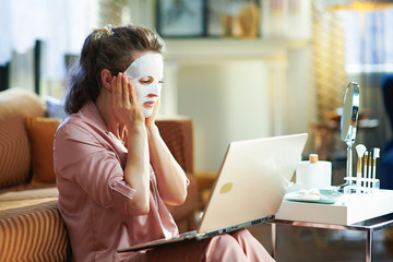 surprised elegant female with facial mask using website