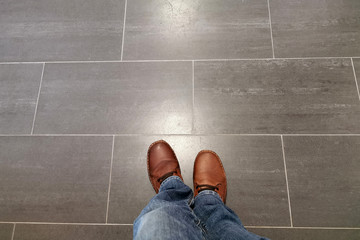 Legs in jeans and red shoes against the background of the tiled floor Fotomurales