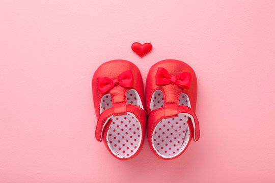 Bright red baby shoes with heart on light pink table background. Pastel color. Closeup. Top view.