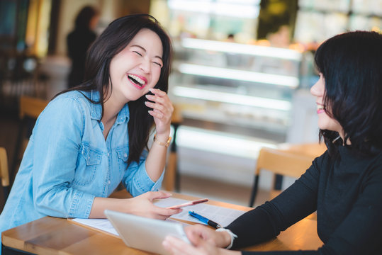 Two happy young attractive Asian women talking together with tablet and paperwork at coffee shop in the morning