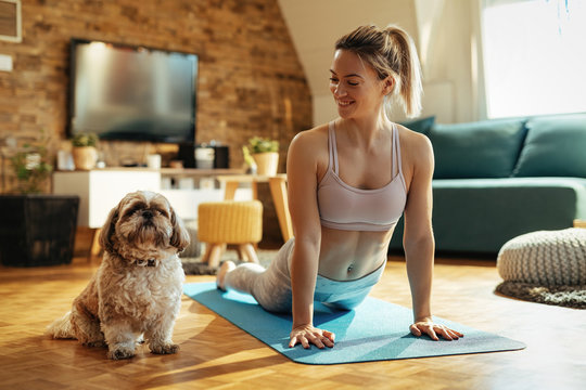 Happy athletic woman with a dog practicing Yoga at home.
