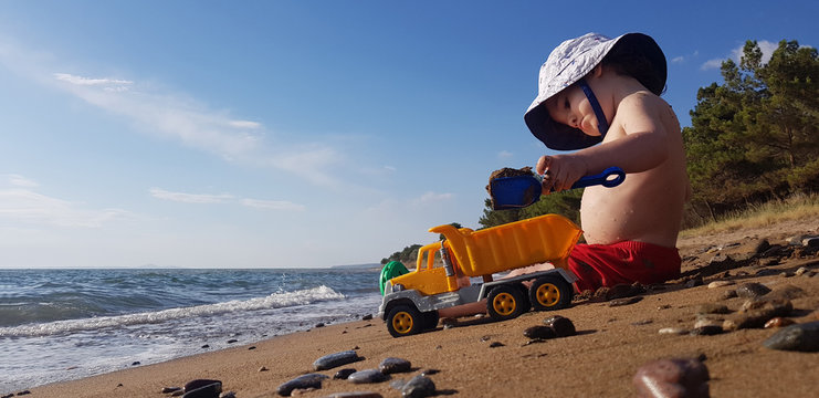 a little boy playing with toy truck and shovel on the beach on a hot summer day