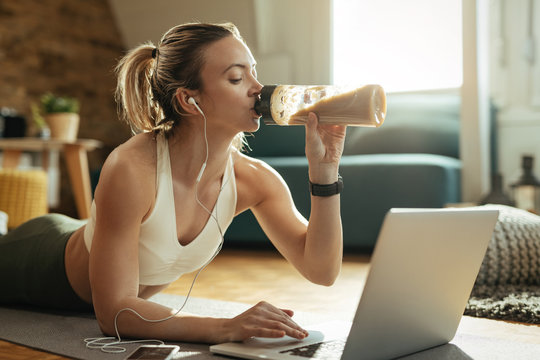 Young athletic woman drinking protein shake while using laptop on the floor.