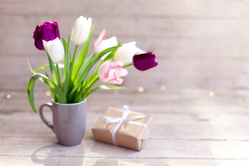 Fotomurales - Spring flowers and gift box at wooden background. Blooming tulips in gray cup. Pink, white, lilac and purple bouquet in vase. Cozy still life. Copy space.