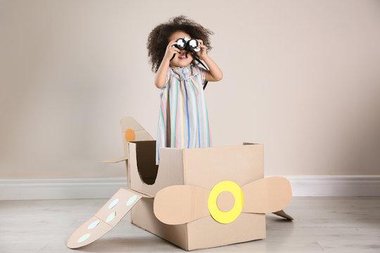 Cute African American child playing with cardboard plane and binoculars near beige wall