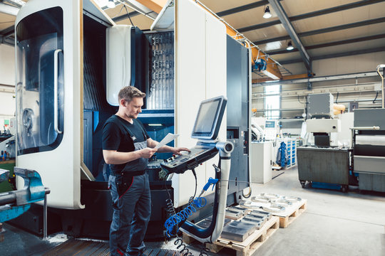 Worker in metal industry operating a modern cnc lathe
