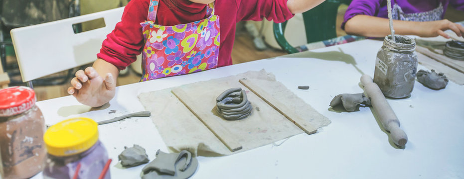 Portrait of little artist working with clay