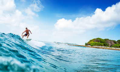Wall Mural - Young man surfs ocean wave in Maldives