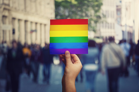 LGBT community member holding a protest banner with pride flag over a crowded street background. Human rights concept, stop discrimination. Rainbow symbol, equality between genders social issue.